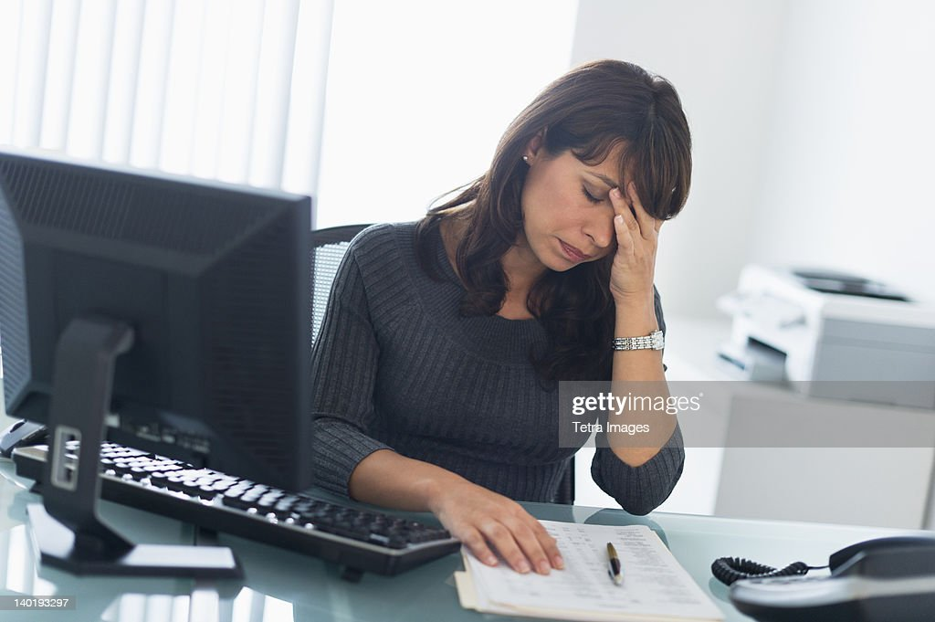 USA, New Jersey, Jersey City, Business woman using computer, looking tired : Stock Photo