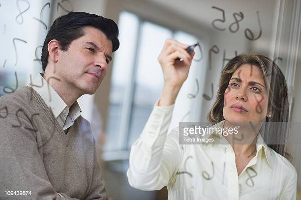 USA, New Jersey, Jersey City, Businessman and woman writing calculations on glass