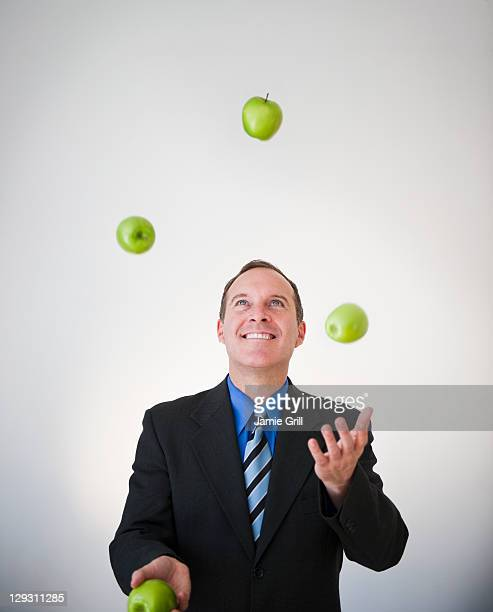 USA, New Jersey, Jersey City, Businessman juggling apples