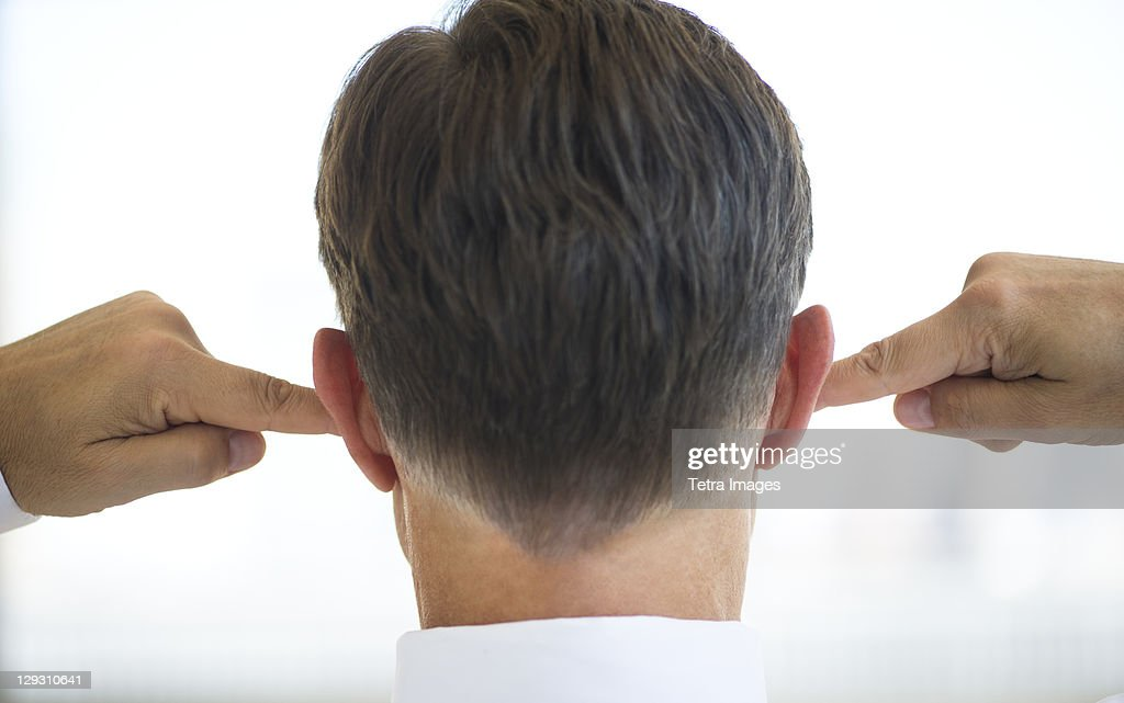 USA, New Jersey, Jersey City, Businessman plugging ears
