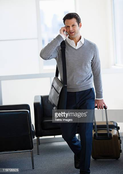 USA, New Jersey, Jersey City, businessman pulling suitcase and talking on mobile phone in airport lounge