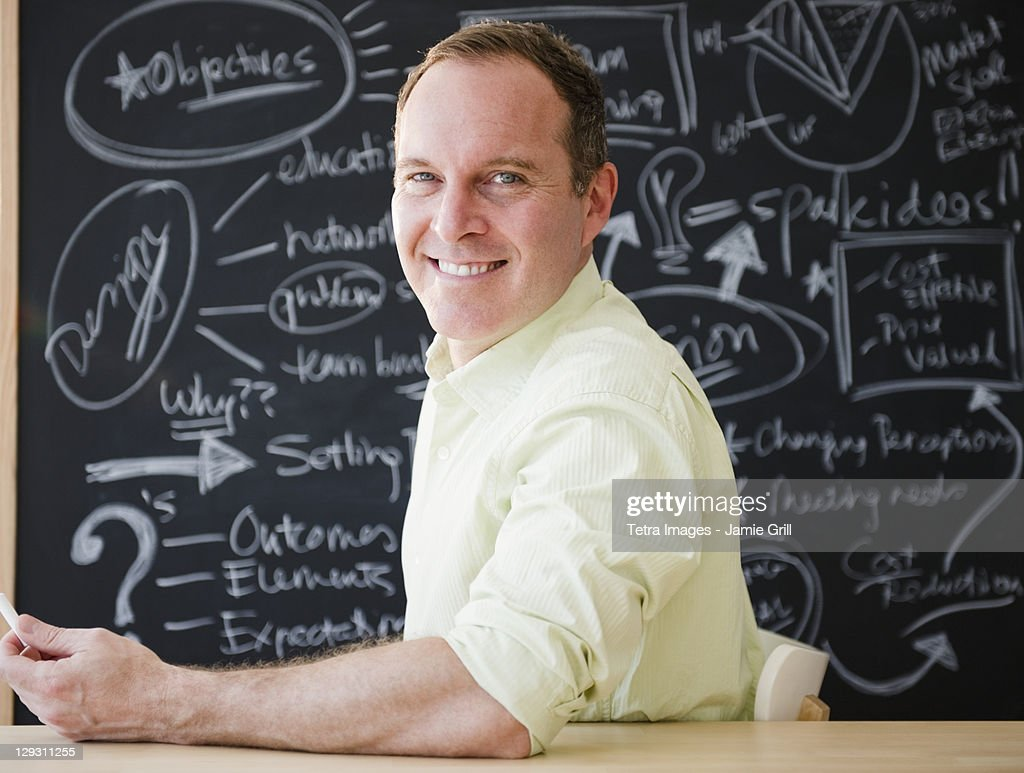 USA, New Jersey, Jersey City, Businessman sitting at table against blackboard : Stock Photo