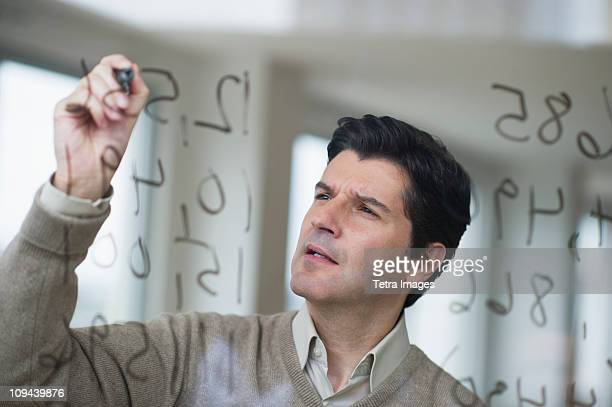 USA, New Jersey, Jersey City, Businessman writing calculations on glass