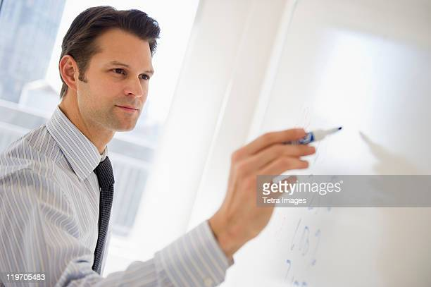 USA, New Jersey, Jersey City, businessman writing on whiteboard