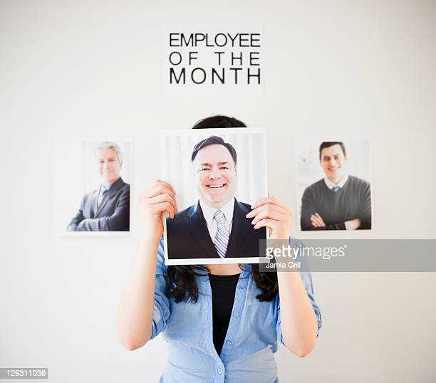 USA, New Jersey, Jersey City, Businesswoman holding photos of men to her face