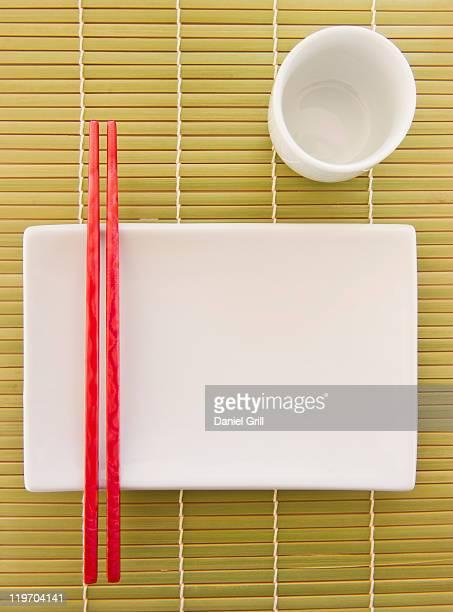 USA, New Jersey, Jersey City, chopsticks, plate and mug on bamboo mat