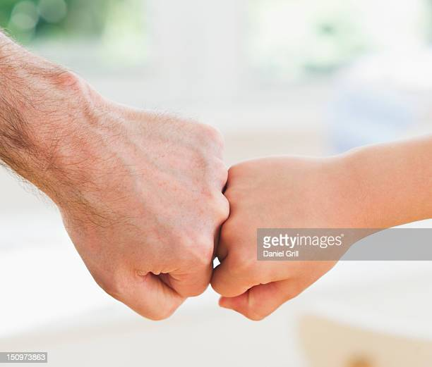 USA, New Jersey, Jersey City, Close up of father's and son's (10-11 years) hands doing fist bump