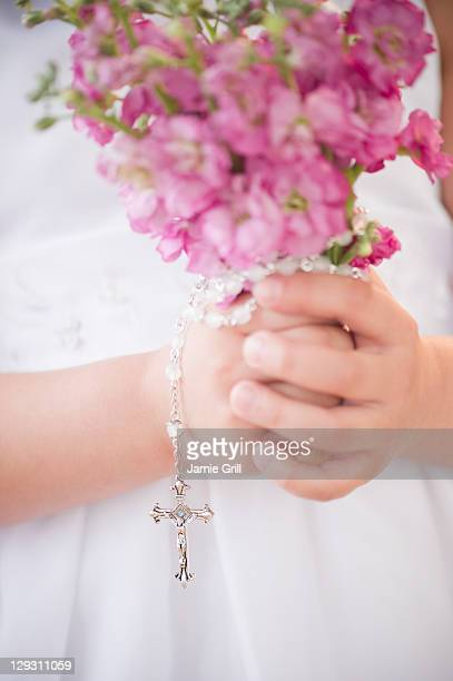 USA, New Jersey, Jersey City, Close up of girl's (8-9) hands holding flowers and rosary beads
