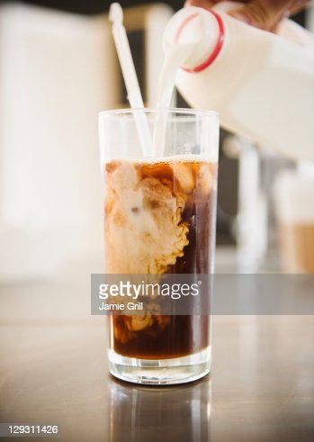 USA, New Jersey, Jersey City, Close up of hand pouring milk into iced coffee
