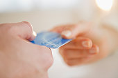 USA, New Jersey, Jersey City, Close up of man's and woman's hands holding credit card
