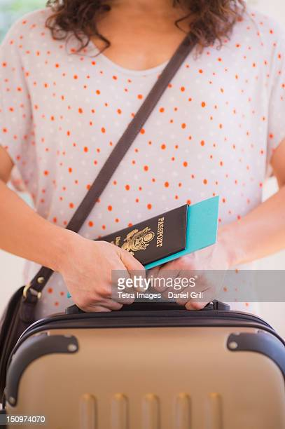 USA, New Jersey, Jersey City, Close up of woman holding luggage and passport