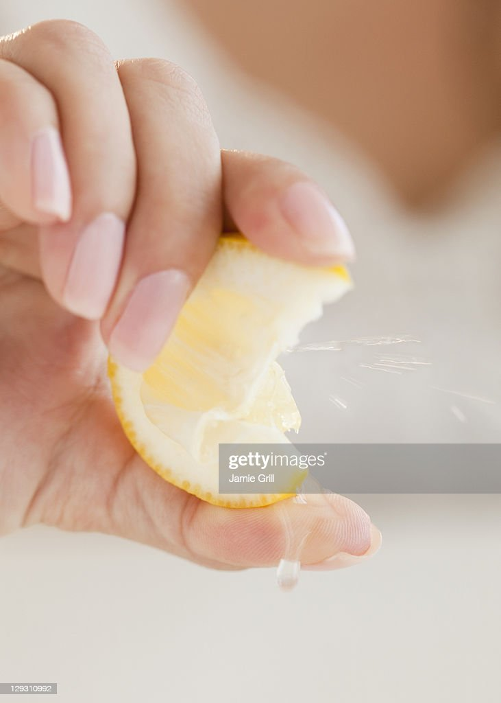 USA, New Jersey, Jersey City, Close up of woman's hand squeezing lemon