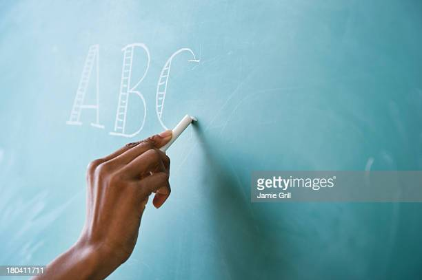 USA, New Jersey, Jersey City, Close up of woman's hand writing alphabet on blackboard
