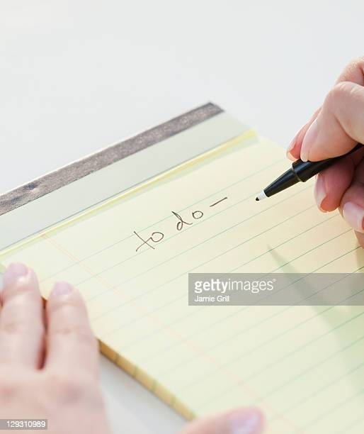 USA, New Jersey, Jersey City, Close up of woman's hands writing list of things to do