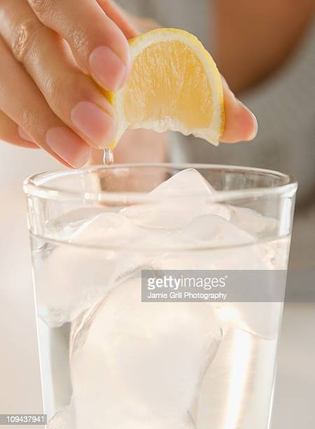 USA, New Jersey, Jersey City, Close-up view of woman's hand squeezing lemon into refreshness drink