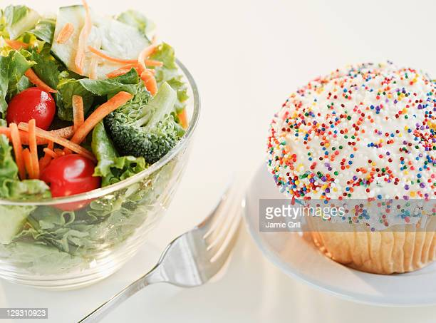 USA, New Jersey, Jersey City, Comparison of cupcake and bowl of salad