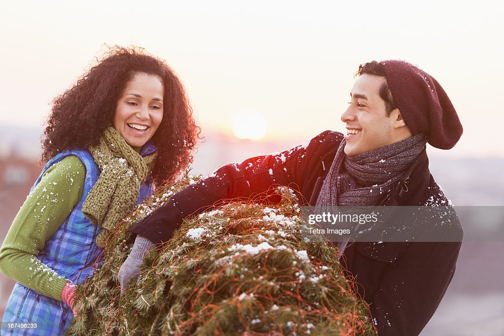 USA, New Jersey, Jersey City, Couple carrying christmas tree : Stock Photo