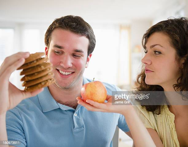 USA, New Jersey, Jersey City, Couple holding cookies and apple