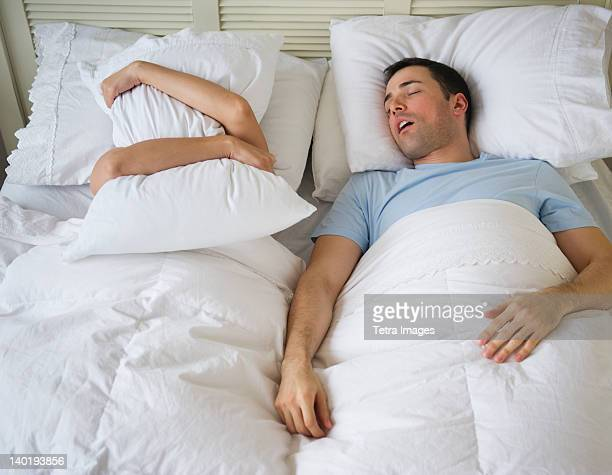 USA, New Jersey, Jersey City, Couple in bed, man snoring