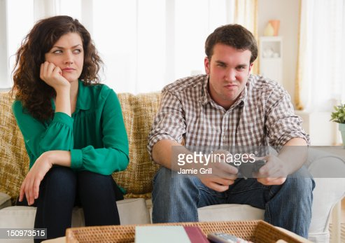 USA, New Jersey, Jersey City, Couple sitting on sofa, man playing video game