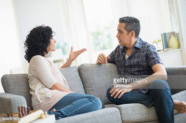 USA, New Jersey, Jersey City, Couple talking on sofa