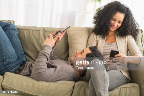 USA, New Jersey, Jersey City, Couple using digital tablet and mobile phone on sofa : Stock Photo