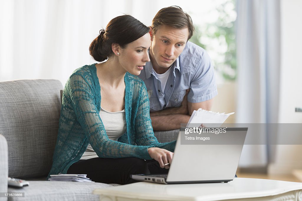 USA, New Jersey, Jersey City, Couple using laptop together to pay bills : Stock Photo