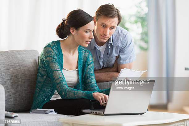 USA, New Jersey, Jersey City, Couple using laptop together to pay bills