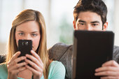 USA, New Jersey, Jersey City, Couple using tablet pc and smartphone