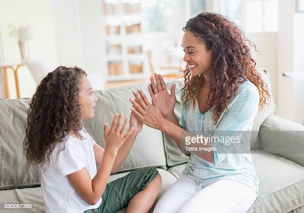 USA, New Jersey, Jersey City, Daughter (8-9) and mother playing clapping game