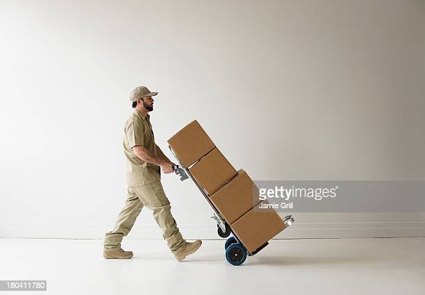 USA, New Jersey, Jersey City, Delivery man walking with push cart