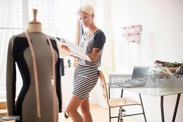 USA, New Jersey, Jersey City, Designer looking at sketchbook in studio