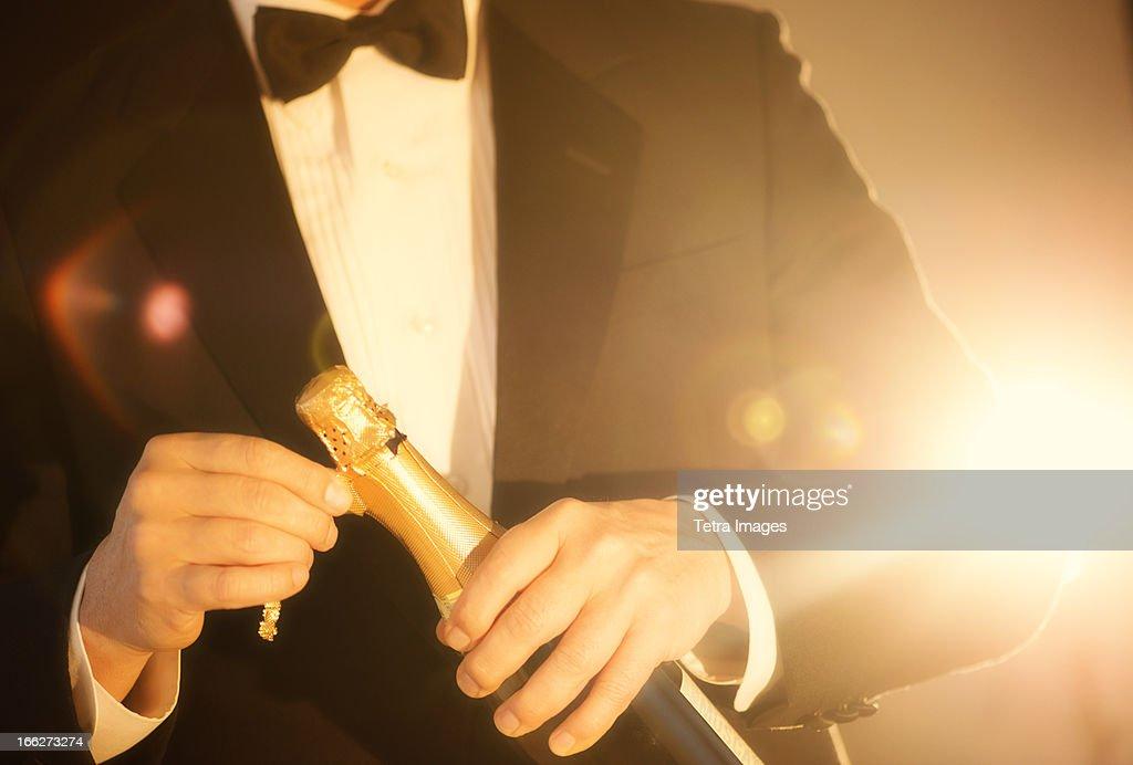 USA, New Jersey, Jersey City, Elegant man opening champagne