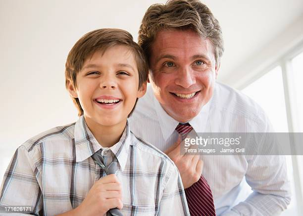 USA, New Jersey, Jersey City, Father and son (8-9) adjusting ties