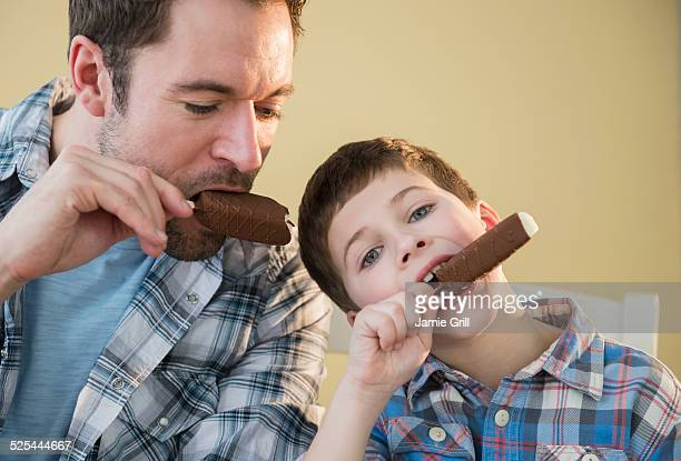 USA, New Jersey, Jersey City, Father and son (8-9) eating ice creams