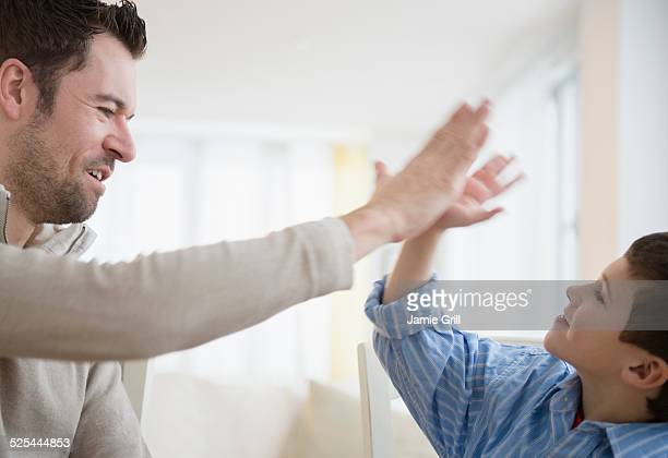 USA, New Jersey, Jersey City, Father and son (8-9) high fiving