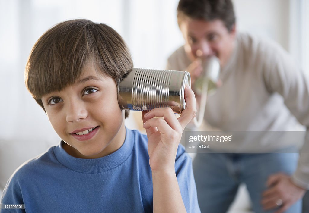 USA, New Jersey, Jersey City, Father and son (8-9) playing with tin can phone : Stock Photo