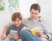 USA, New Jersey, Jersey City, Father and son (10-11 years) sitting on sofa with book and digital tablet