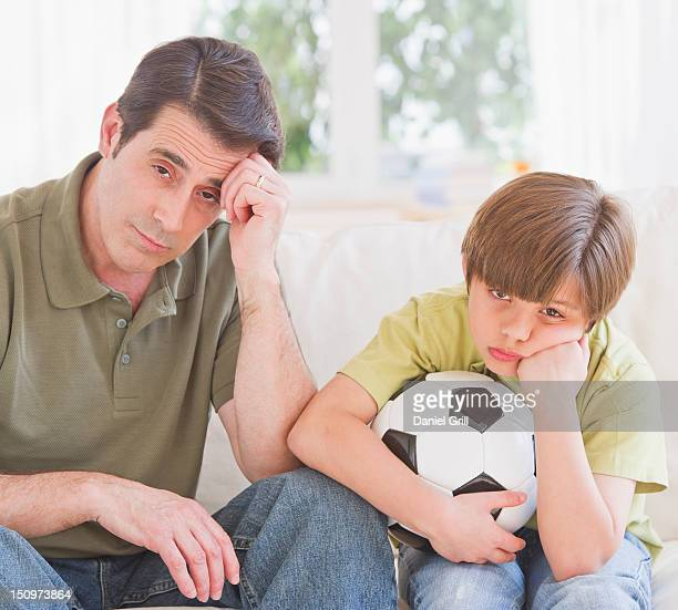USA, New Jersey, Jersey City, Father and son (10-11 years) watching football match with sadness