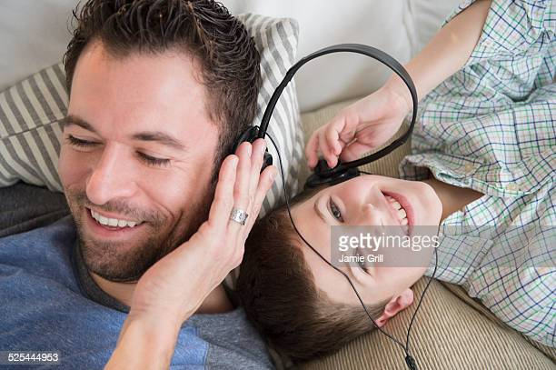 USA, New Jersey, Jersey City, Father listening to music with son (8-9)