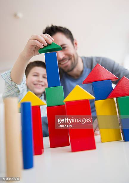 USA, New Jersey, Jersey City, Father stacking blocks with his son (8-9)