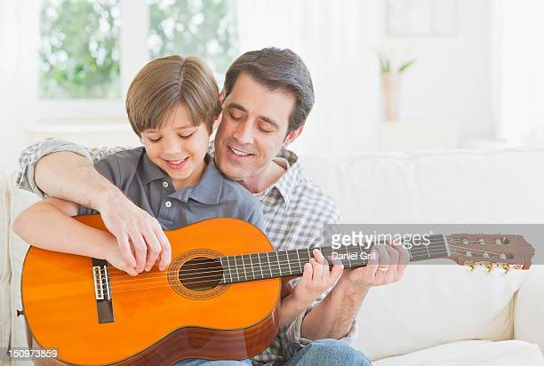 USA, New Jersey, Jersey City, Father teaching son (10-11 years) how to play acoustic guitar