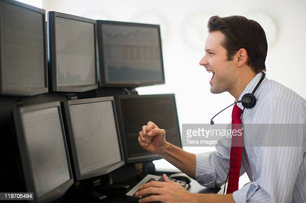 USA, New Jersey, Jersey City, financial worker analyzing data displayed on computer screen