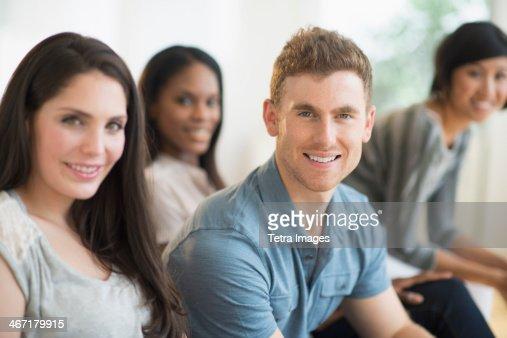 USA, New Jersey, Jersey City, Friends sitting on sofa : Stock Photo
