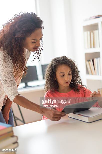 USA, New Jersey, Jersey City, Girl (8-9) and teacher using digital tablet in classroom
