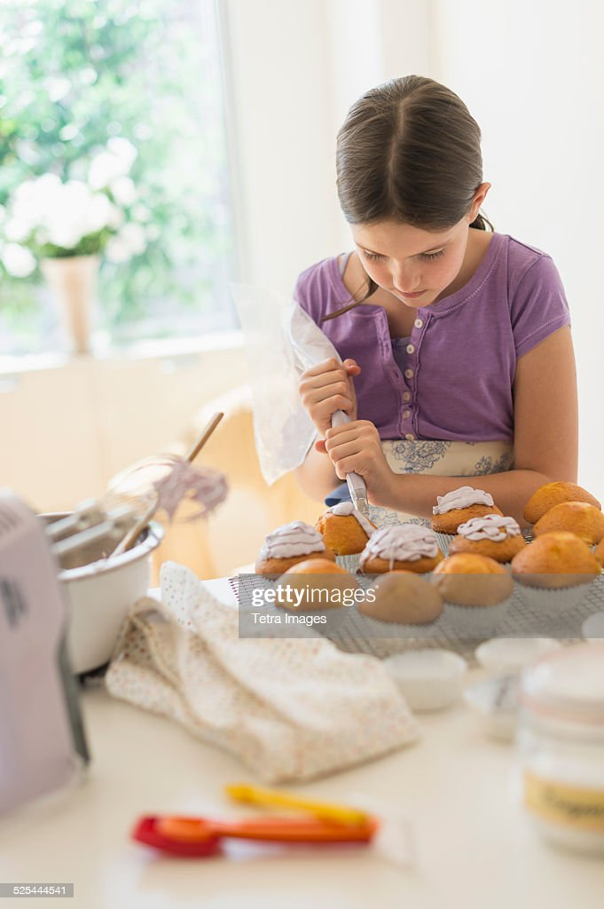 USA, New Jersey, Jersey City, Girl (10-11) decorating cakes