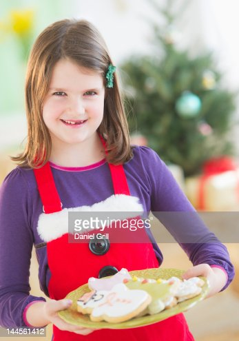 USA, New Jersey, Jersey City, Girl (8-9) holding plate with gingerbread cookies : Stock Photo