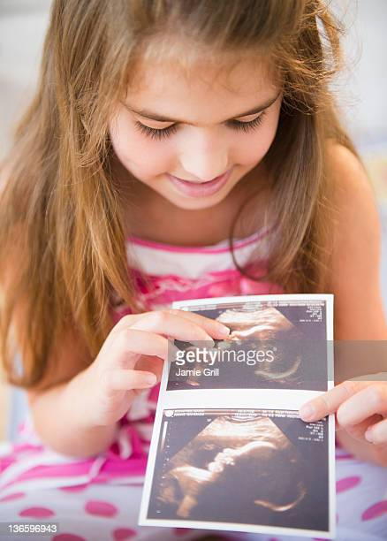 USA, New Jersey, Jersey City, Girl ( 6-7) watching sonogram picture