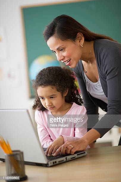 USA, New Jersey, Jersey City, girl (6-7) with female teacher using laptop in classroom