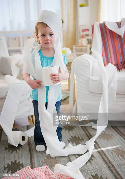 USA, New Jersey, Jersey City, Girl (2-3) wrapped with toilet paper standing in living room